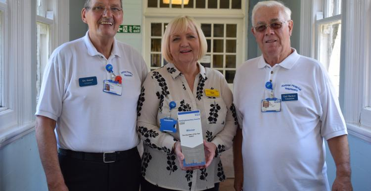 Photo of Aintree Hospital volunteers Eric, Gail and Ged holding their award