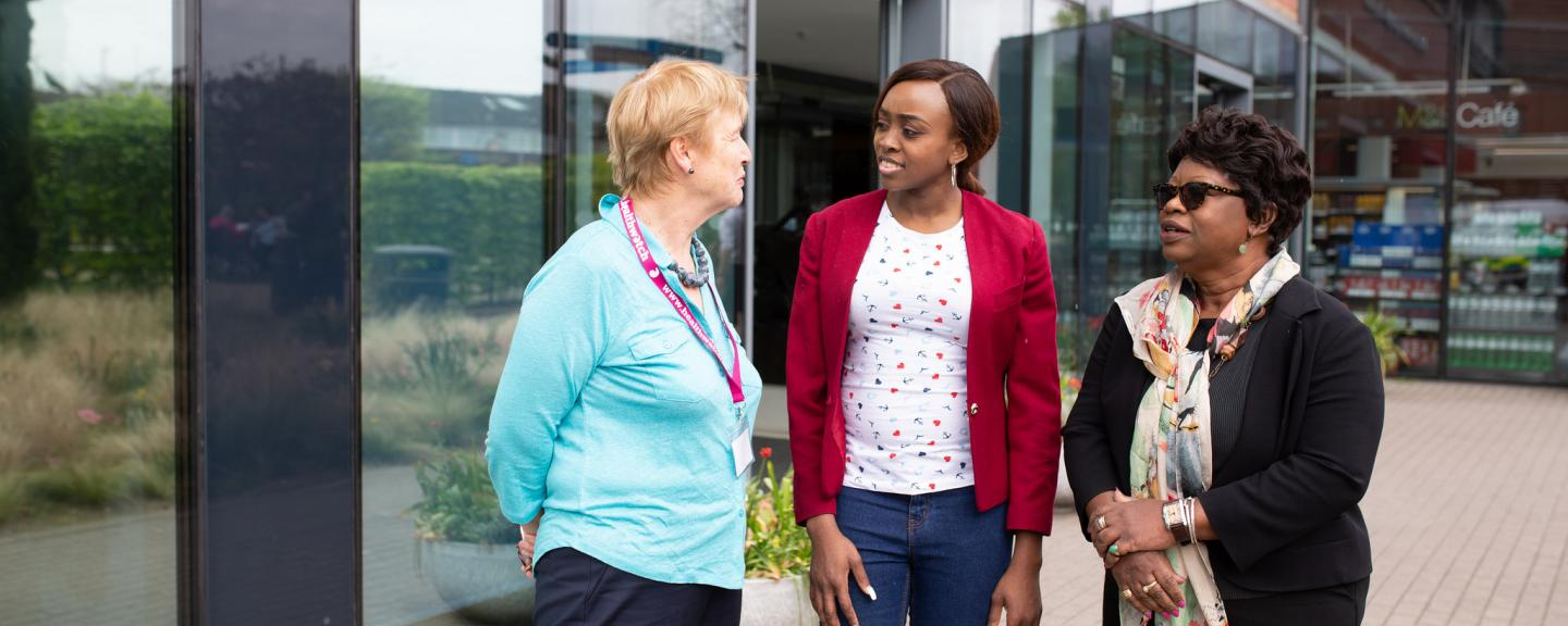Picture of three women speaking outside a hospital building