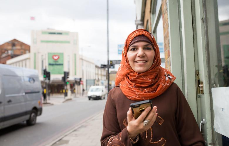 woman standing in the street holding a mobile phone