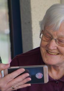A close up of and older woman, with short white hair, smiling at a mobile phone. The phone is being held up by a younger women, wearing a surgical-style face mask.